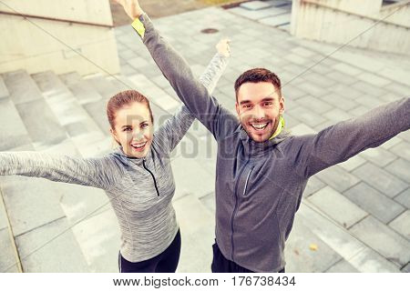 fitness, sport, people and lifestyle concept - happy smiling couple outdoors on city street