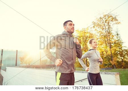 fitness, sport, people, exercising and lifestyle concept - happy couple running upstairs on city stairs