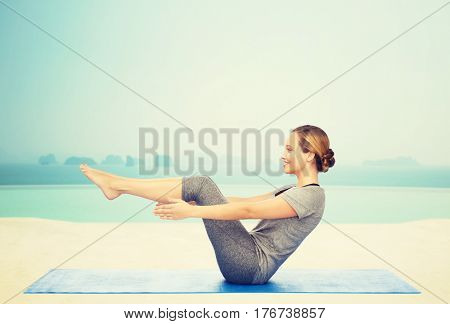 fitness, sport, people and healthy lifestyle concept - woman making yoga in half-boat pose on mat over infinity edge pool at hotel resort background