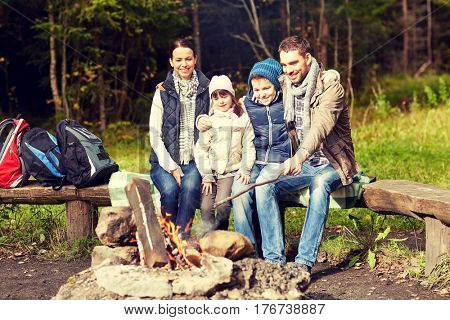 camping, travel, tourism, hike and people concept - happy family sitting on bench at camp fire in woods