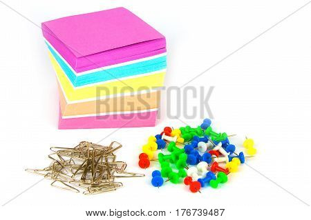 Colorful note paper, pins and heap of metal clips isolated on a white background. Close up