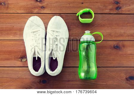 sport, fitness, healthy lifestyle and objects concept - close up of sneakers, bracelet and water bottle on wooden floor