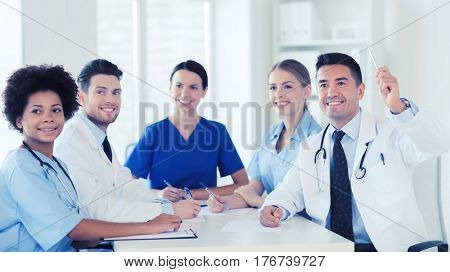 hospital, profession, people and medicine concept - group of happy doctors meeting and asking questions on conference at hospital