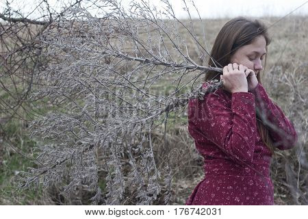 girl in the red folk dress gathers dry grass
