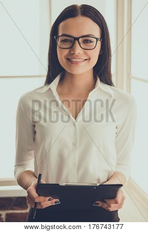 Beautiful female psychologist in eyeglasses is holding a folder looking at camera and smiling while standing in her office