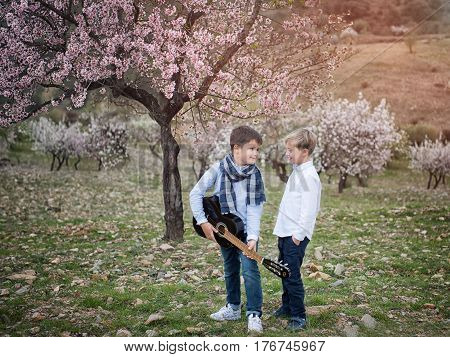 Young friends in the park playing the guitar and singing