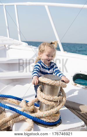 Small Baby Boy With Happy Face On Boat With Rope