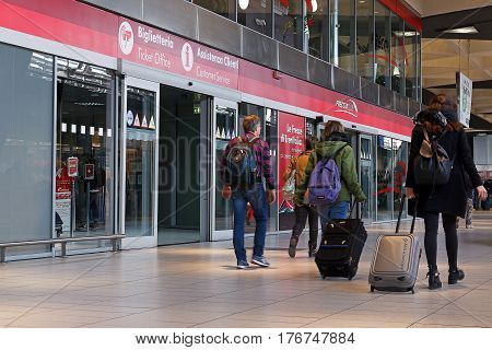 Naples Italy - March 13 2017: Ticket office and customer support in the Garibaldi central train station travelers with baggage walking in the hallway in front and enter and exit the office.
