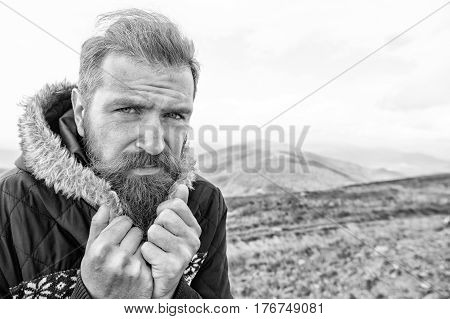 bearded man long beard brutal caucasian hipster with moustache on serious face unshaven guy with stylish hair getting beards haircut cower from cold on mountain top on cloudy sky black and white poster