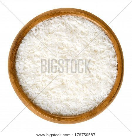 Coconut flakes in a wooden bowl, also called copra. Dried and grated flesh or meat of the coconut kernel. Edible, raw and organic food. Isolated macro photo close up from above on white background.
