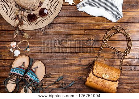 Top View Of Swimming Pants, Straw Hat, Sunglasses, Sandals And Bag On Table