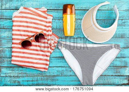 Top View Of Bikini Bottom, Sunglasses, Cap And Sunscreen On Blue Wooden Table, Summer Concept