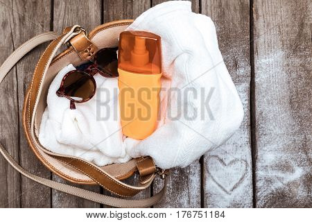 Top View Of Towel, Sunscreen And Sunglasses In Bag On Wooden Tabletop With Heart Sign. Summer Holida