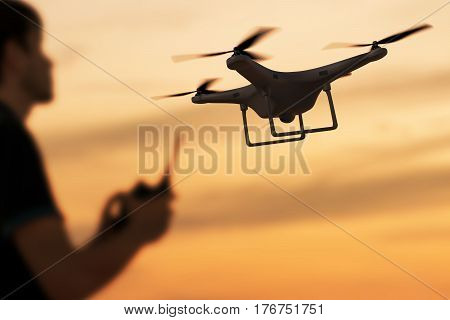 Man Is Controlling Flying Drone At Sunset. 3D Rendered Illustrat