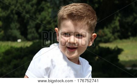 Portrait of a todler smiling. plaing in the garden. small boy has fun in the park. expresion of  happiness.