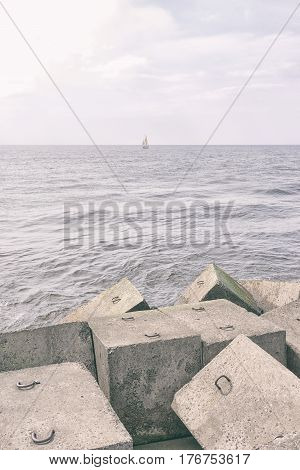 Concrete cubes around a stone breakwater and a yacht in the Baltic sea near the horizon