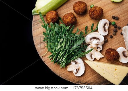 Vegetarian falafel and fresh green vegetables and mushrooms on a wooden board also spices zucchini chopped mushrooms greens and cheese