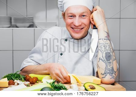 Man is going to cook a vegetarian. Healthy food. Different kinds of vegetables. Cook. Portrait of a smiling man.