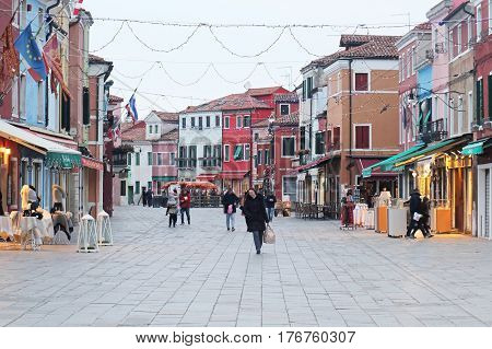 BURANO ITALY - JANUARY 10; Tourists and locals walking around large square inside Burano island Italy - January 10 2017: Burano is an island in the Venetian Lagoon situated 7 kilometres from Venice.