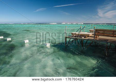 Pier with chaise longues in the sea in resort. Summer vacation. View at a clear sea with turquoise water.