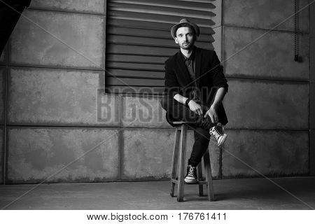 Stylish l guy in jacket and sneakers in black and white hat sits on a high chair. Black and white background