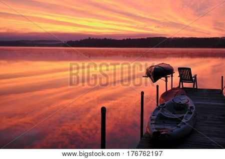 Spectacular sunrise reflects on a pristine New England lake.