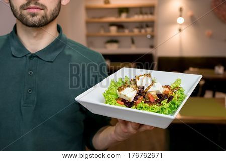 A waiter with a Greek salad on a white plate in his hand. Handsome young waiter in a green shirt at restaurant