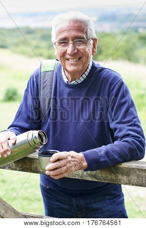 Senior Man On Hike Having Hot Drink