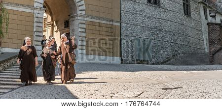 POLAND, KRAKOW- JULY 03: Group of female monks, polish catholics walking downtown on a warm sunny day in Krakow Poland on July 03, 2015