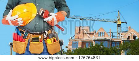 Mature contractor and hoisting crane. Building frame poster