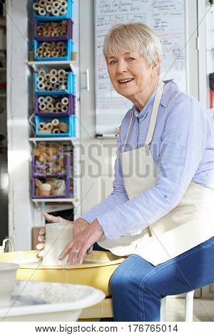 Senior Woman Working At Pottery Wheel In Studio