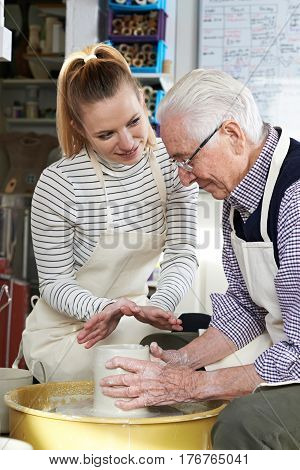 Senior Man With Teacher In Pottery Class