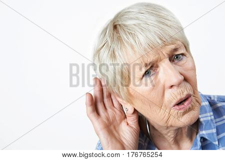 Studio Shot Of Senior Woman Suffering From Deafness