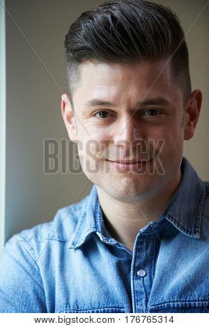 Indoor Head And Shoulders Portrait Of Smiling Man