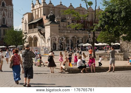 POLAND, KRAKOW- JULY 02: Tourists walking on the ancient streets romanesque buildings on a hot sunny day in Krakow Poland on July 02, 2015