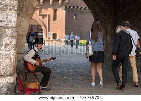 POLAND, KRAKOW- JULY 01: Local Polish man dressed in national clothes plays guitar in the arch of famous building in Krakow Poland on July 01, 2015