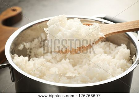 Spoon with cooked rice over metal saucepan, closeup