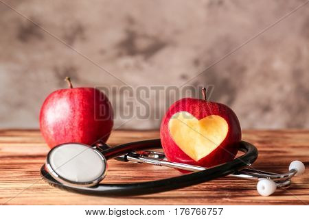 Red apples and stethoscope on wooden table