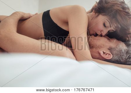 Intimate Couple Hugging And Kissing In Bed