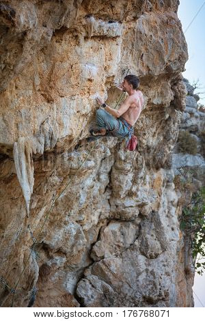 Male rock climber struggling on challenging route on cliff