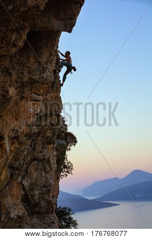 Young man climbing vertical cliff at sunset view of sea and islands below