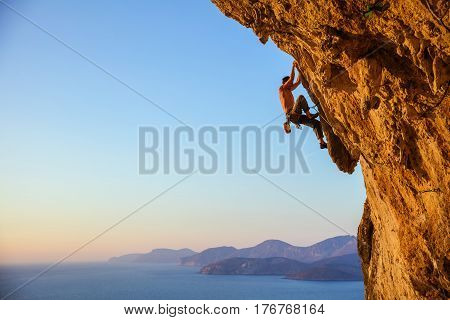 Young man struggling to climb challenging route on cliff at sunset view of coast below