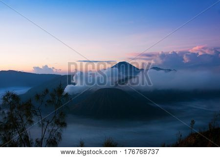 White smoke coming out of volcanoes surrounded by white clouds of mist and a clear blue sky seen at a distance in the morning from Mount Penanjakan at the Tengger Semeru National Park in East Java Indonesia.