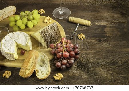 A photo of a wine and cheese tasting, with bread, grapes, corkscrew and glasses, with a place for text
