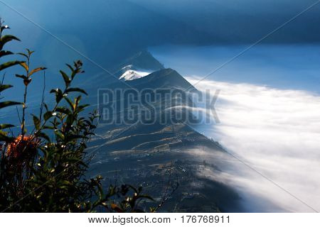 White clouds of mist covering village seen at a distance in the morning from Mount Penanjakan at the Tengger Semeru National Park in East Java Indonesia.