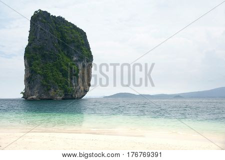 Big high rock cliff filled with green vegetation surrounded by turquoise blue colored ocean water next to a tropical white sand beach with horizon view at midday Krabi Thailand.