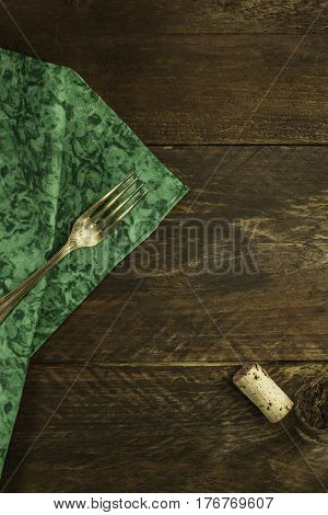 An overhead photo of a vintage fork and a wine cork on a dark wooden background texture with copy space