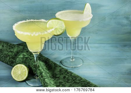 Lemon Margarita cocktails with wedges of lime on a vibrant turquoise background with copy space. Selective focus, slightly toned image