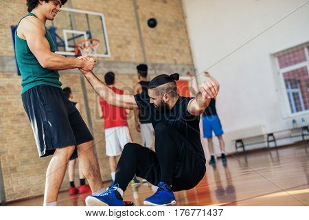 Photo of basketball players helping each other on the basketball court.