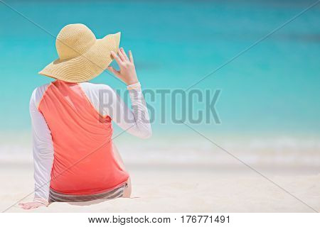back view of young woman in rashguard and sunhat enjoying the perfect caribbean beach and protecting her skin from sun exposure during summer vacation copyspace on the right